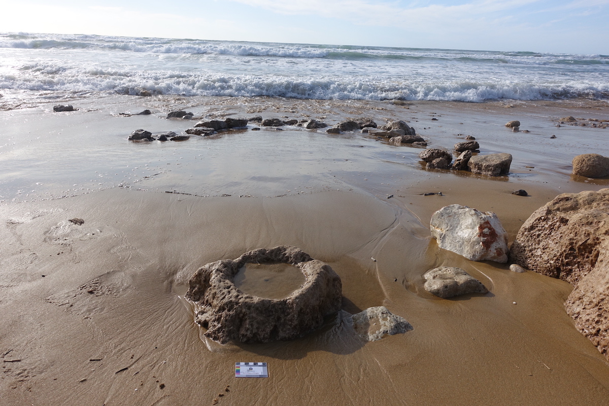 Coastal erosion in Tel Hreiz and the exposure of site features: a stone bowl and a wall segment.