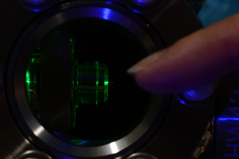 Photograph of a levitated particle. The particle is made visible by green laser light illumination. A finger, pointing at the particle, illustrates the size of the experiment.