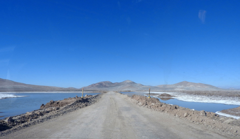 A road in the Atacama Desert surrounded by natural lagoons.